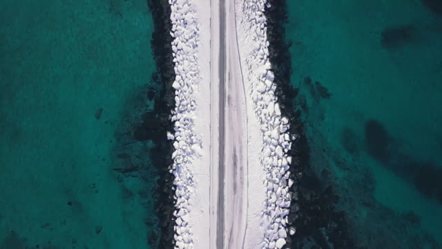 Bird's eye view of car driving on arctic winter road