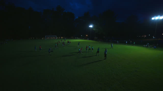 birds eye view of children playing an organized game of flag football in the dark - sporting term stock videos & royalty-free footage