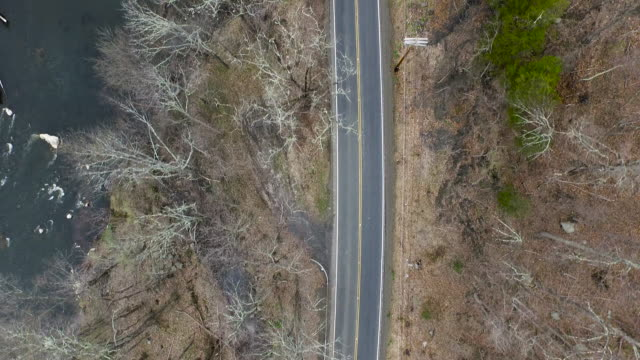 Bird's eye view of empty one lane road running parellel to river in upstate New York
