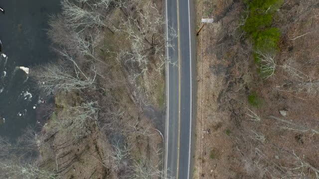 bird's eye view of empty one lane road running parellel to river in upstate new york - bare tree stock videos & royalty-free footage