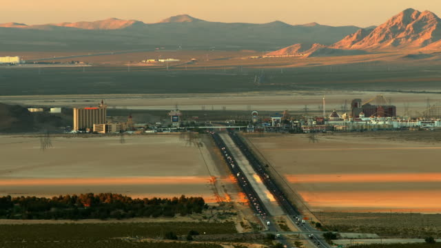 t/l ws birds eye view of heavy traffic through ivanpah valley on interstate 15 at california nevada state line with casino resort primm in far distance with hotels and casinos on both sides of the interstate  /  primm, nevada, usa - us state border stock videos & royalty-free footage