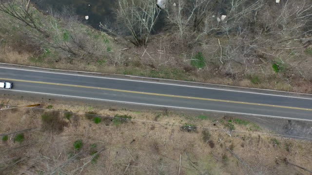 Bird's eye view of light traffic on one lane road on wintery day