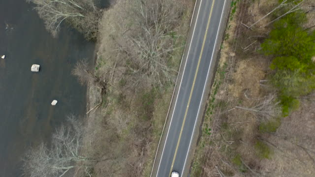 Bird's eye view of one lane road running parallel to a river