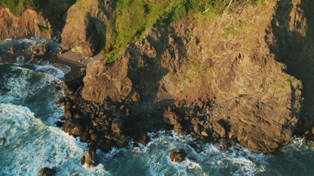 birds eye view of rocky coastline and small beach beneath dramatic cliffs on oregon coast - oregon coast stock videos & royalty-free footage