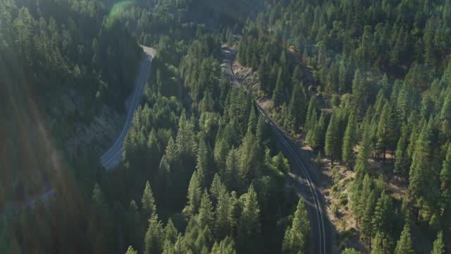 stockvideo's en b-roll-footage met birds eye uitzicht op treinrails, rivier en weg in feather river canyon - sunny