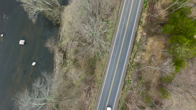 bird's eye view of truck one-lane road, parallel to a rocky river - bare tree stock videos & royalty-free footage