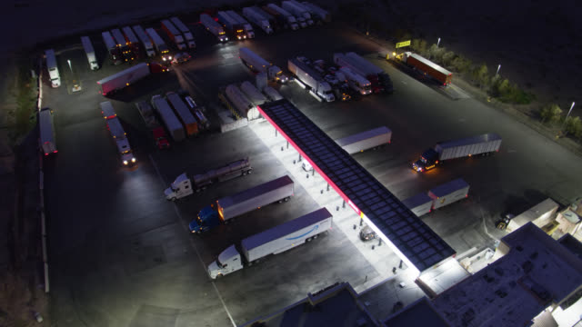 vidéos et rushes de birds eye view of trucks refueling at rest stop at night - sud ouest américain