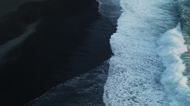 birds eye view of waves hitting black sand beach - black sand stock videos & royalty-free footage