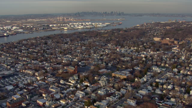 bird's eye view over the rooftops of staten island flying toward manhattan in new york city. - staten island stock videos and b-roll footage