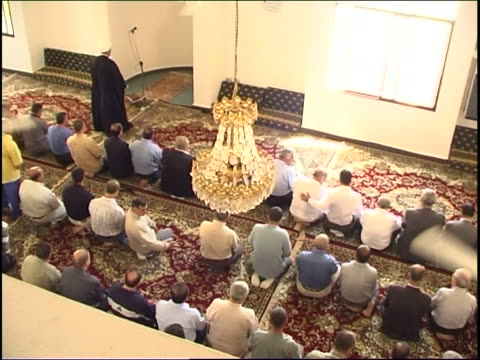 vídeos de stock e filmes b-roll de bird's eye view panleft from shia men praying in the central hall of a mosque to women praying in their section segregated from the men - mesquita