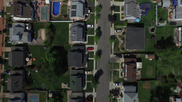 Bird's eye view panning slowly up over single family homes in a New Jersey suburb