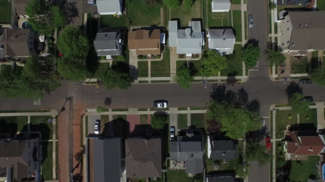 vídeos de stock, filmes e b-roll de bird's eye view panning to the right over single family homes in a new jersey suburb - community