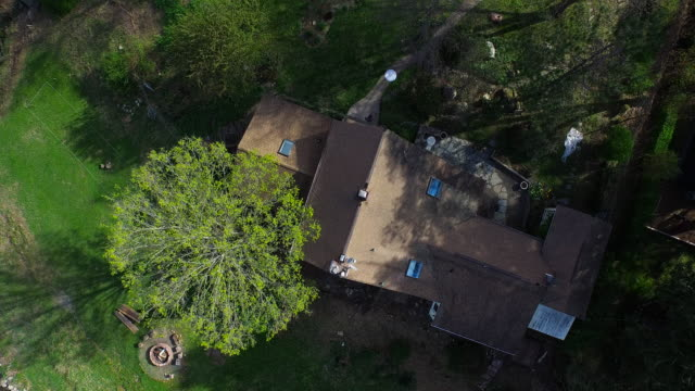 Bird's eye view pulling away from house and trees along the river edge