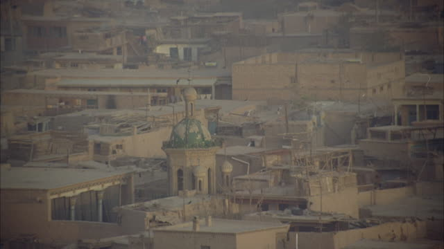 birds fly above a domed spire in a neighborhood in afghanistan. - afghanistan stock videos & royalty-free footage