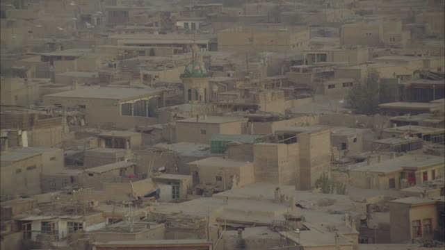 birds fly above dusty buildings in a neighborhood in afghanistan. - afghanistan stock videos & royalty-free footage