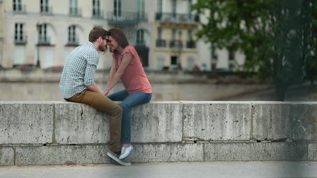 birds fly by as affectionate young couple hold hands and nuzzle foreheads by the seine. - two people stock videos & royalty-free footage