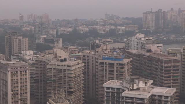 Birds fly over tall buildings surrounding Back Bay in Mumbai, Maharashtra, India.