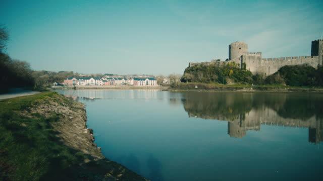 ws birds flying over moat surrounding pembroke castle / pembroke, wales, united kingdom - ペンブローク点の映像素材/bロール