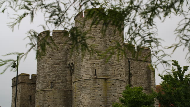 vídeos de stock e filmes b-roll de birds rest on the sides of the round towers of canterbury's westgate, kent, uk. - idade media