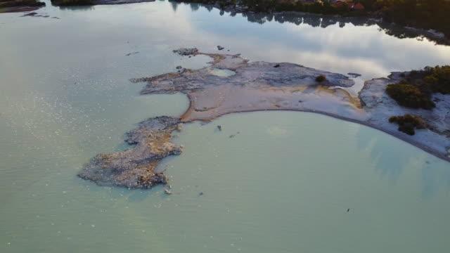 Birds swarm over geothermal hot pools in Lake Rotorua.