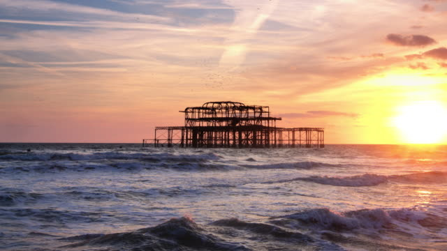 birds swirling around burnt out pier, brighton - 1975 stock videos & royalty-free footage