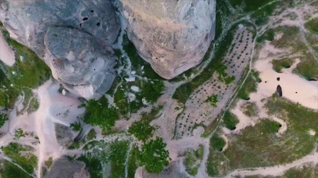 vídeos de stock e filmes b-roll de birdseye of large rocks with houses carved inside - exposto ao ar