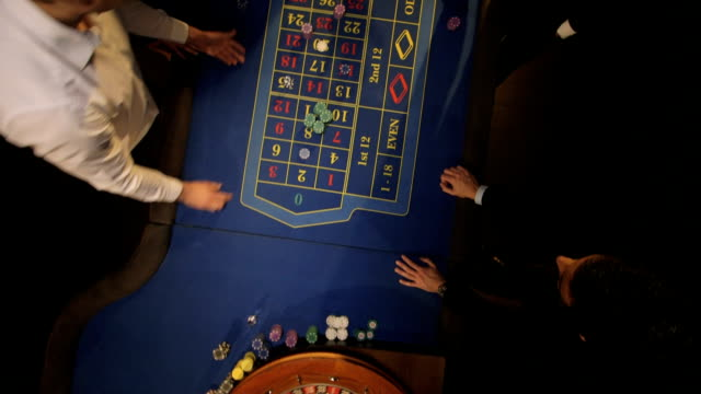 mcu birdseye pan of roulette table and players - roulette stock videos and b-roll footage