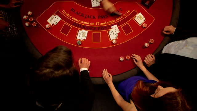 Birdseye Panning CU of Players Gambling in the Casino
