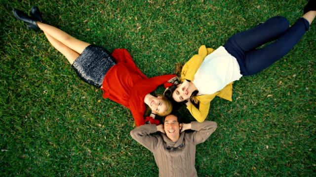bird´s-eye shot of group of three friends laughing over the garden grass - oberteil stock-videos und b-roll-filmmaterial