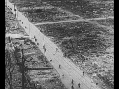 Bird'seye shot people walk ride bicycles on road past demolished landscape after US's atomic bomb hit Hiroshima during World War II / rubble / nurses...