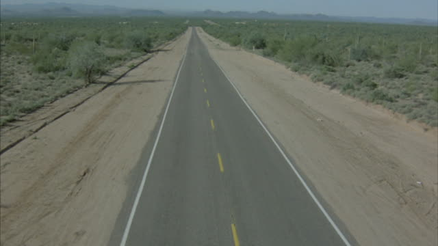 stockvideo's en b-roll-footage met bird's-eye-shot of a car driving on a highway in a desert and mountains. - pan american highway