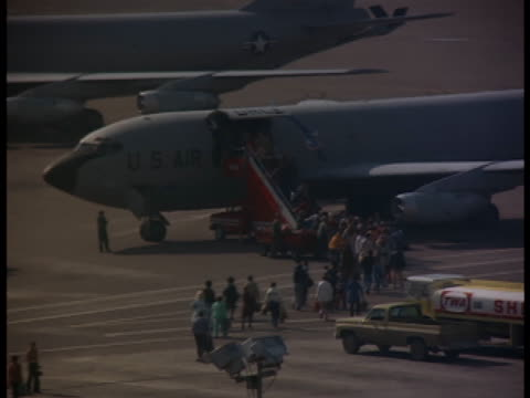 Bird's-eye-shot of an airport landing field as passengers are boarding US Airforce airplanes.
