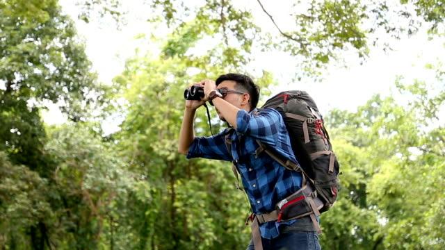 vídeos de stock e filmes b-roll de birdwatching. excited young man birdwatcher use binolcular in rain forest background. chiang mai, thailand. - observar pássaros