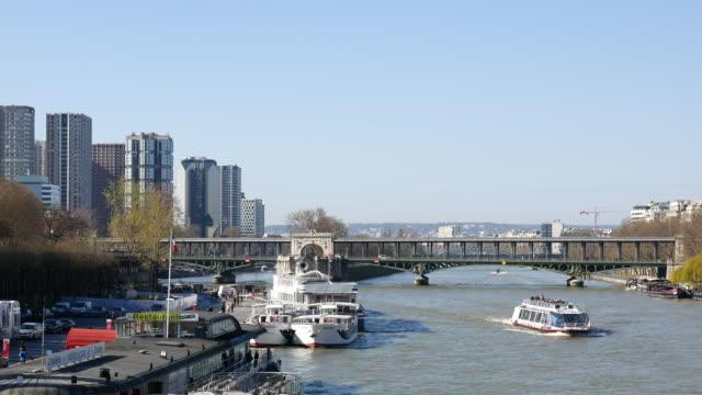 bir-hakeim bridge with metro train and boat in paris, france, 4k(uhd) - pont de bir hakeim stock videos & royalty-free footage