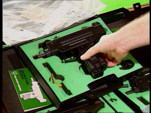 birmingham shootings/ new penalties lib uzi gun on display in case gun picked up from case order ref t06010301 - gun crime stock videos & royalty-free footage