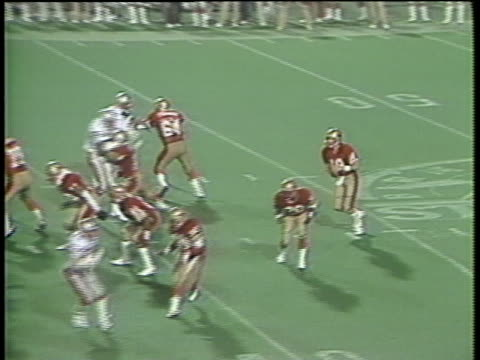 1985 MS ZI Birmingham Stallions snap ball/  HA WS quarterback Cliff Stoudt throwing pass to wide receiver Joey Jones for touchdown against Memphis Showboats/ WS crowd/ MS Jones jumping into teammates' arms/ Birmingham, Alabama