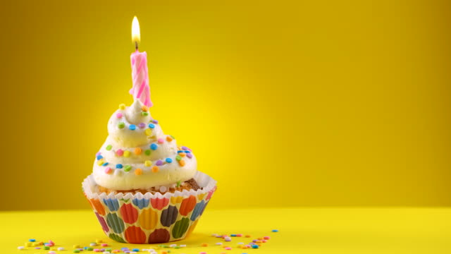 birthday decorated cupcake with a candle and sprinkles - sliding shot - birthday cake stock videos & royalty-free footage