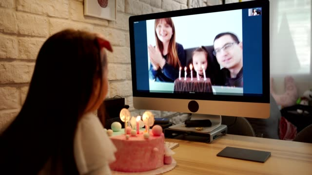 birthday girl blowing birthday candles in home isolation while her family singing her happy birthday song via video app - compleanno video stock e b–roll