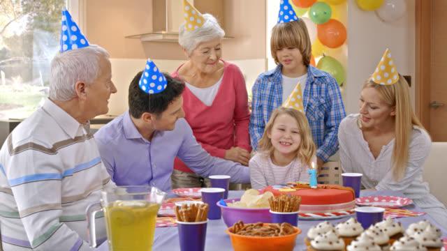 Menina de aniversário a soprar as velas de aniversário para o sétimo