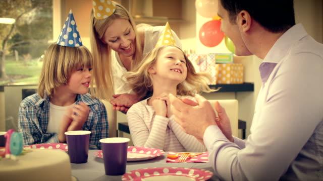 SLO MO Menina de aniversário a soprar as velas de aniversário décimo