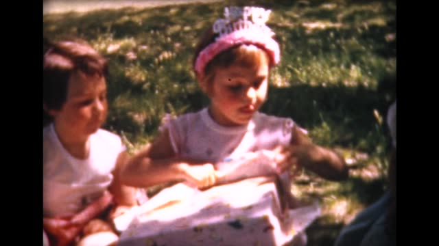 1961 birthday girl opens presents - innocenza video stock e b–roll