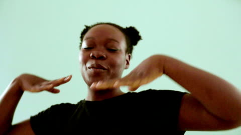bisexual black woman posing and smiling on colourful background - generation z点の映像素材/bロール