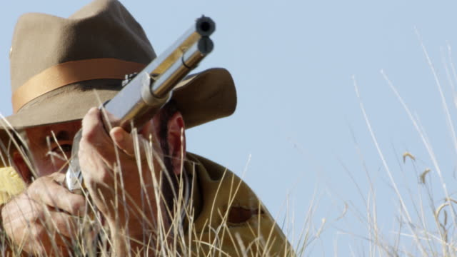 ms bison hunter man firing rifle and lying on grassy landscape / montana, united states  - krabbeln stock-videos und b-roll-filmmaterial
