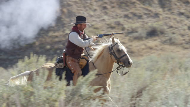 ms pan bison hunter man firing rifle and riding on horse grassy landscape / montana, united states  - one mid adult man only stock videos & royalty-free footage