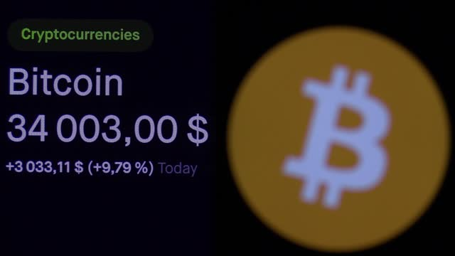 bitcoin digital currency sign is seen on a mobile phone screen in front of its price on a pc screen. bitcoin cryptocurrency for the first time... - blockchain stock videos & royalty-free footage