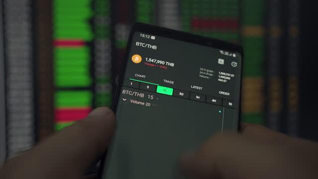 stockvideo's en b-roll-footage met bitcoin is een wereldwijd cryptocurrency en digitaal betalingssysteem. aandelenmarkt, online handelen, handelaar die met smartphone op beurshandelsvloer werkt. - mining