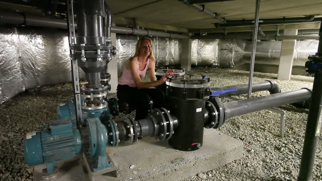 Bizarre engineer thinking happily while relaxing among water pumps