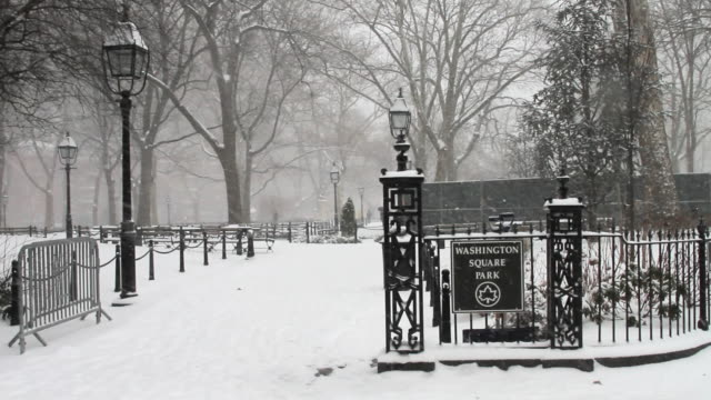 A bizzard scene in Washington Square Park. Shown is the Washington Square Park sign.