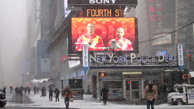 A bizzard scene with traffic in Times Square New York. A police station is shown.
