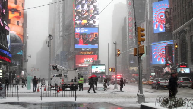 A bizzard scene with traffic in Times Square New York.